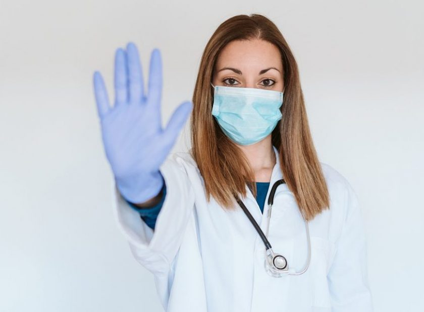 portrait of doctor woman wearing protective mask and gloves indoors. Making a stop sign with hand. Corona virus concept